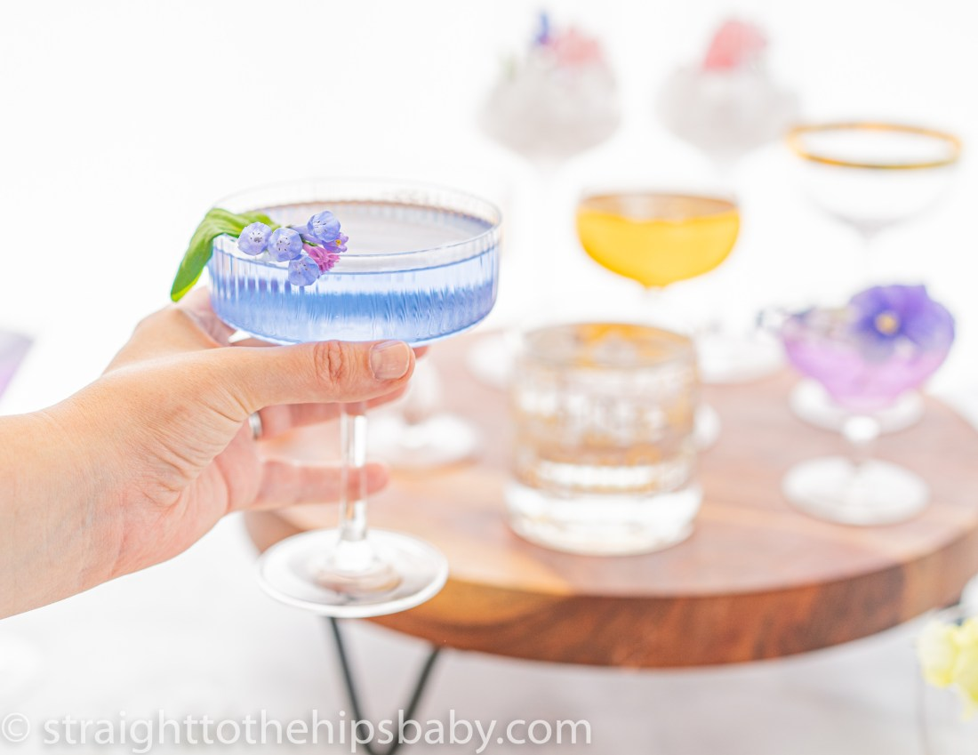 a woman's hand holding a vintage glass cocktail coupe filled with a blue cocktail, garnished with a purple flower. Blurred cocktail glasses are in the background