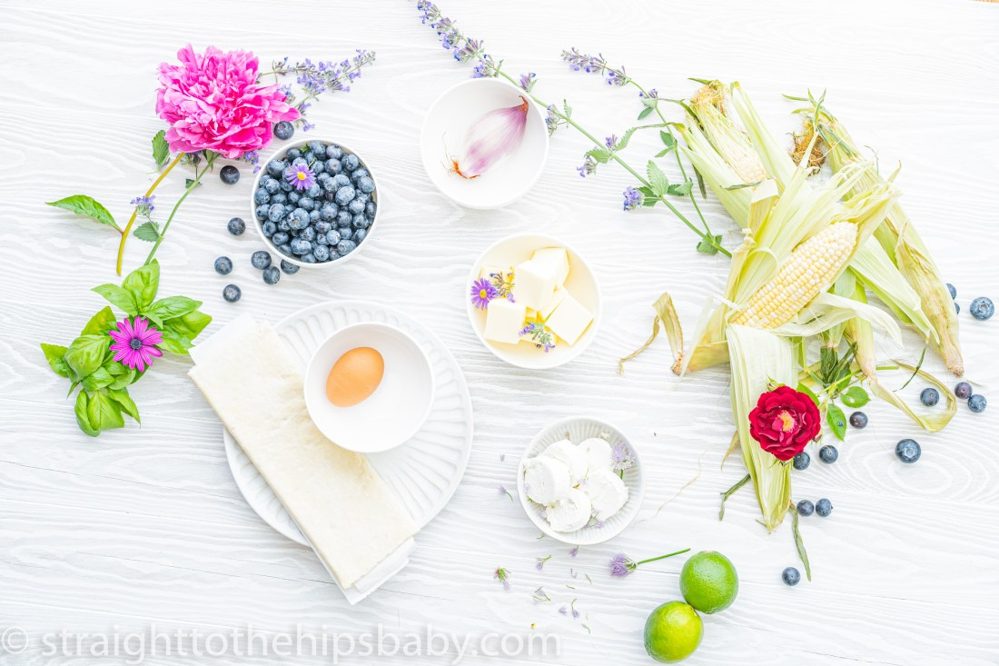 an ingredient flatly with brightly colored corn, blueberries and herbs for puff pastry blueberry and goat cheese bites