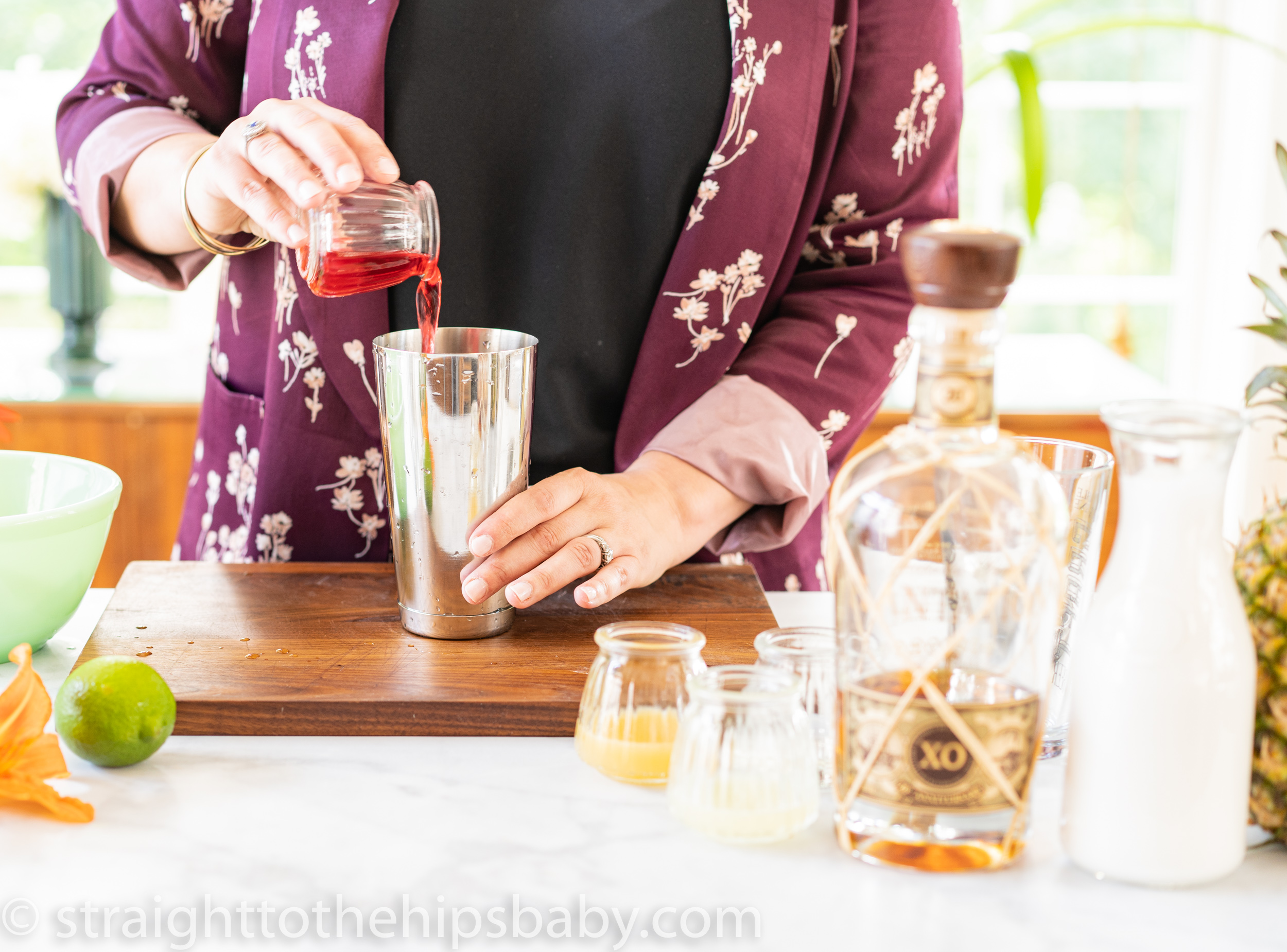 a woman pouring red Hibiscus tea into a cocktail shaker