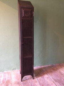 1türiger Spint mit Schrägdach und Lochblech verzierter Tür.
