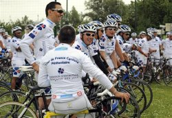 "FILE - This Wednesday June 4, 2009, file photo shows a pack of convicts, joined by their jailers, preparing to take the start from Villeneuve d'Ascq to Valenciennes, northern France, of the prologue of the ""Tour de France Penitentiaire"" for the jailed. Most days, they live behind bars. But last week, a pack of convicts, joined by their jailers, a police escort and a string of support vehicles, embarked upon the inaugural two-week, 2,200 kilometer cycling trek across the Gallic countryside, organized by French prison administrators. (AP Photo)"