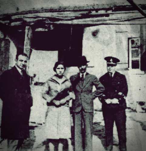 """Στην αυλή του σπιτιού, όπου συνέβησαν τα περίεργα τηλεκινητικά φαινόμενα. Από τα δεξιά προς τα αριστερά, διακρίνονται στη φωτογραφία ο Αστυνόμος Σαρρηγιάννης, ο Άγγελος Τανάγρας, η 18χρονη Άννα Κουβουτσάκη και ο συντάκτης της εφημερίδας """"ΑΚΡΟΠΟΛΙΣ"""", Στούρνας"""