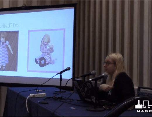 """Myself, sitting alone on a panel table speaking into the mic. Behind me a projector is playing a slide that reads """"The Haunted Doll"""". There is a MAGfest logo in the bottom right corner."""