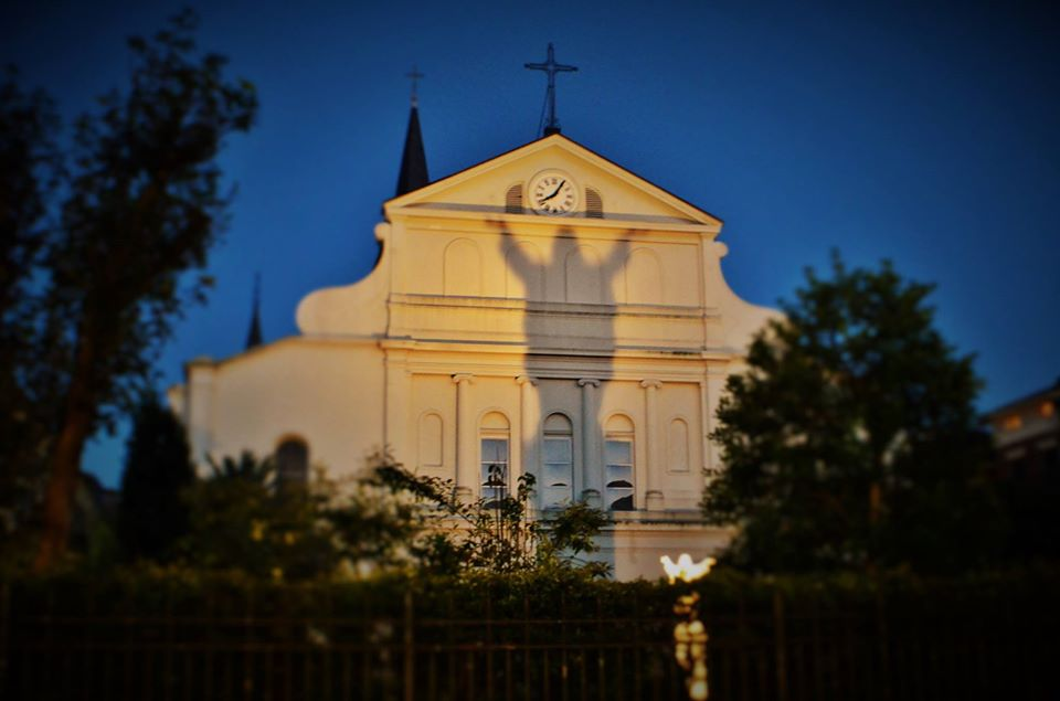 Touchdown Jesus casts his shadow behind St Louis Cathedral in the French Quarter of New Orleans