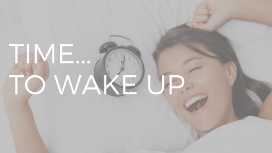 """Time to wake up"" written in white text over a light-skinned woman with brown hair in bed yawning with her alarm clock beside her."