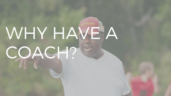 "white text reading ""why have a coach"" over photo  of a baseball coach in red hat"
