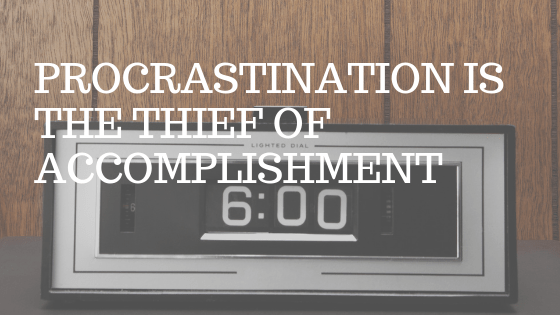"an old-timey clock radio in a wood paneled room. White text over picture reading ""procrastination is the thief of accomplishment"""