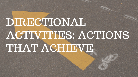 """photo is of an orange arrow painted on a street with white text over top reading """"directional activities: actions that achieve"""""""