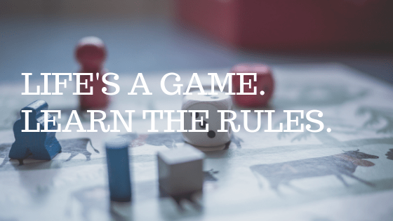 """Game board with dice, with white text reading """"life's a game, learn the rules"""""""