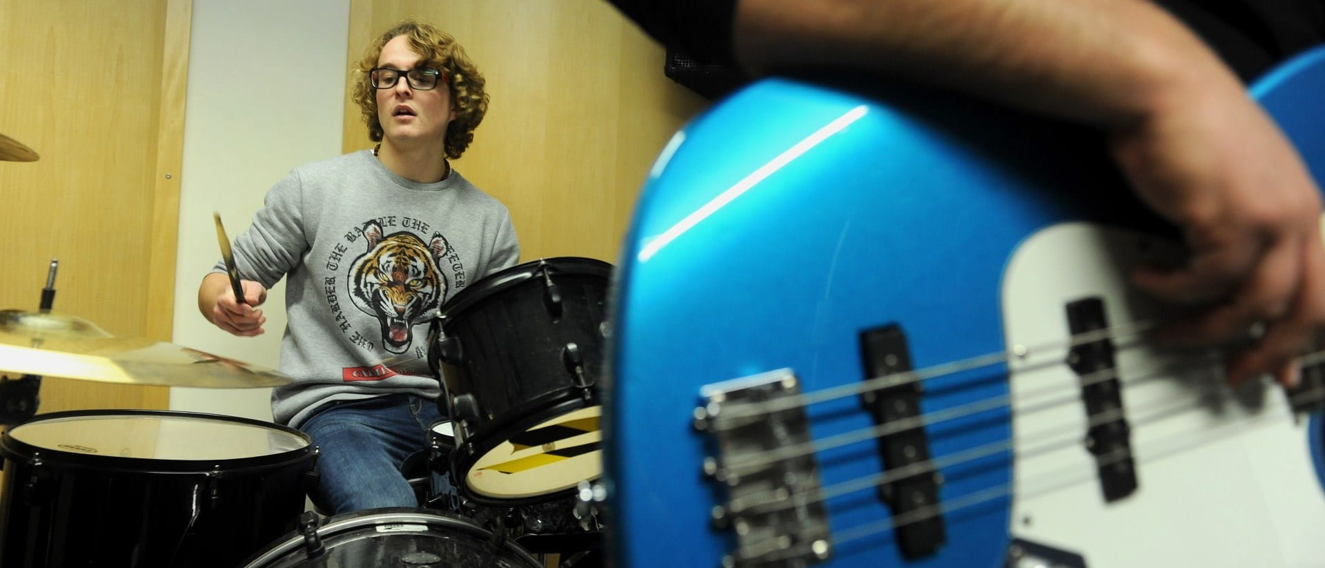 Music student plays drums in a recording studio.