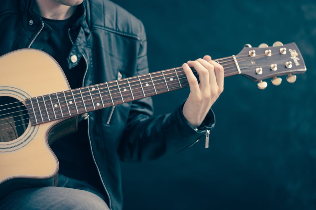 Music tutor Jobs on the Central Coast. A music tutor holding his acoustic guitar, ready to teach his students.