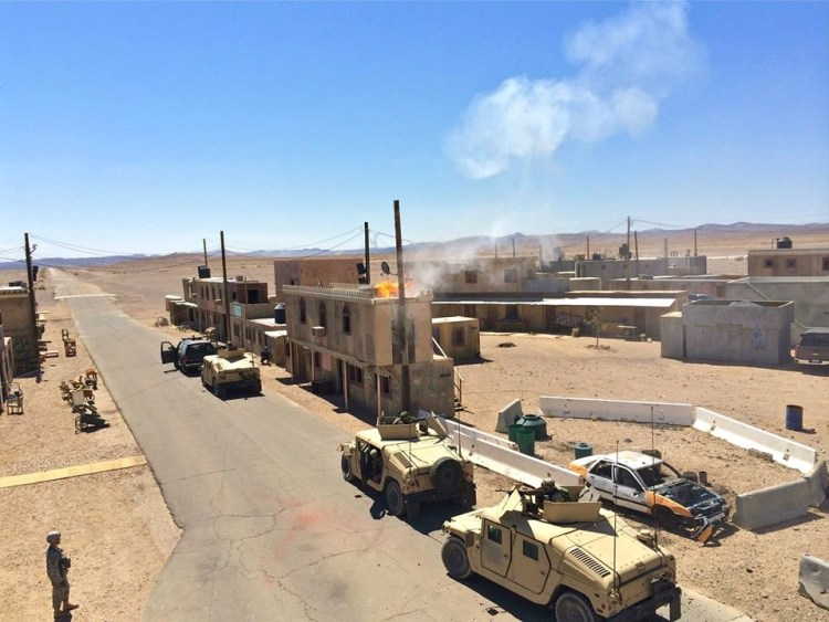 Soldiers use Fort Irwin's facsimile villages to practice clearing structures and navigating unmapped, roofed alleyways through cities without clear satellite communications links.