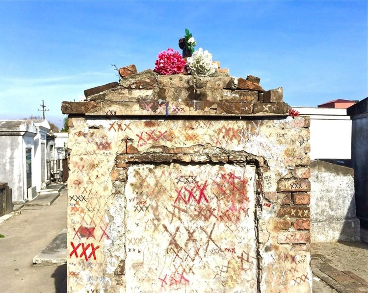 "A Faux Laveau - Decades ago, someone started a rumor that if people wanted Marie Laveau, the voodoo priestess to grant them a wish, they had to draw an ""X"" on the tomb, turn around three times, knock on the tomb, yell out their wish, and if it was granted, come back, circle their ""X,"" and leave Laveau an offering."