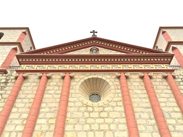 A close-up view of the pediment situated above the chapel entrance at Mission Santa Barbara and its unique ornamental frieze