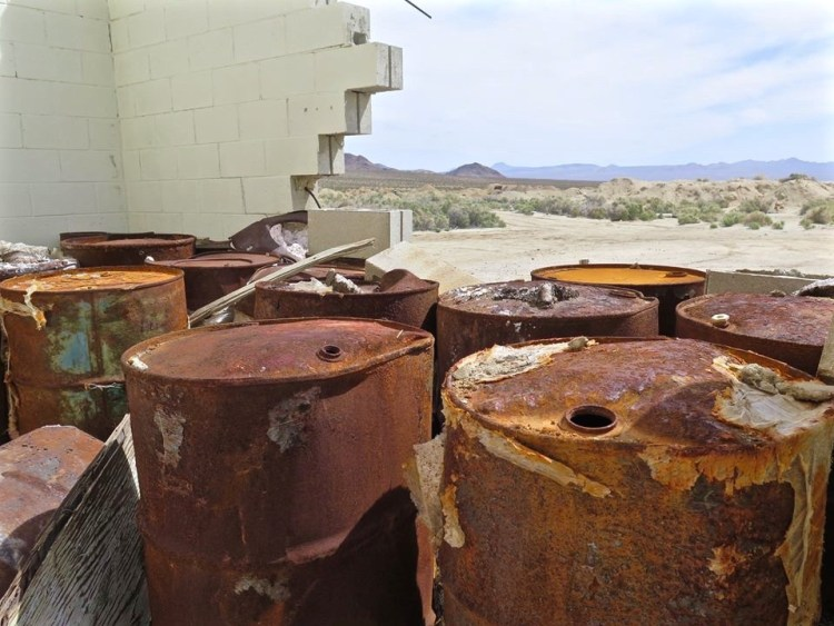 Corroded barrel storage outside the mill building.