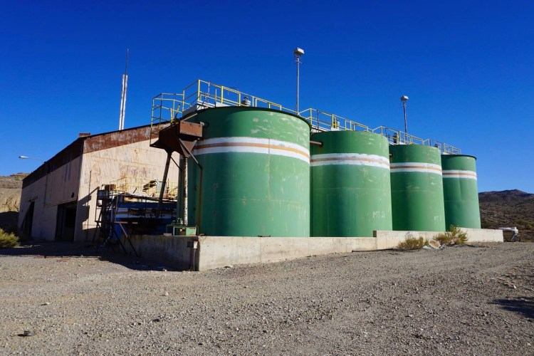 A tank farm with four approximately 30,000 gallon ASTs and associated clarifiers and other unidentified process vessels is located outside along the western side of the mill building.
