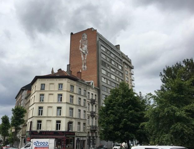 Porte de Hal, un vieil homme nu est représenté sur un haut mur, une main sur son sexe ©Streep.fr