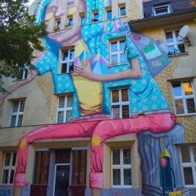 Os Gémeos hat eine überdimensional große Figur auf eine Hausfassade gemalt