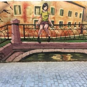 Deih malte ein Mural auf dem ein Mädchen zu sehen ist, das in Venedig auf einer Brücke sitzt