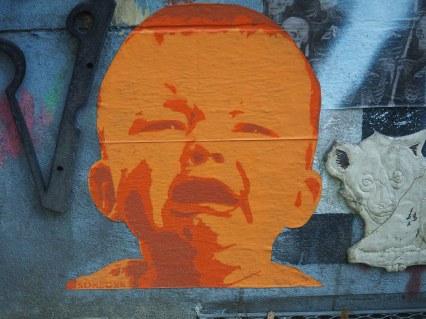 ein paste up von Someone das ein weinendes Baby in orange zeigt
