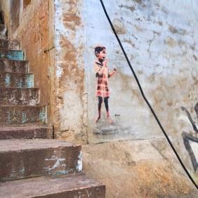 """Tonas kleiner Junge """"Sweetz"""" klebt an einer Wand neben einer Treppe"""
