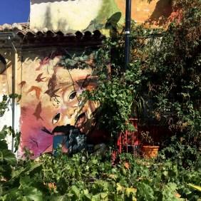 Eine stark bewachsene Hauswand mit einem Mural von El Niño de las Pinturas dass ein lachendes Kind zeigt