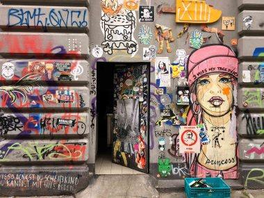 eine Hauswand mit geöffneter Tür die mit Stencils, Graffiti und Paste ups übersät ist. an der Seite prangt ein überlebensgroßer Frauenkopf von El Bocho