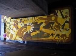 Mural unter einer Brücke von SatOne, das im Vordergrund ein springendes Reh zeit-in gelb