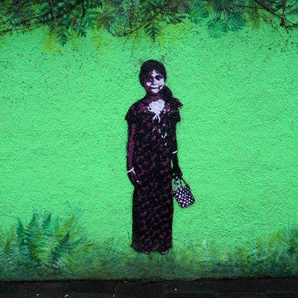 ein junges Mädchen von Tona als Stencil auf einer grüngestalteten Wand