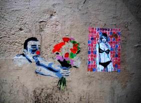 ein Clown streckt einer nur mit Bikini bekleidet jungen Frau einen Blumenstrauß entgegen