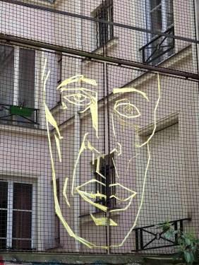 mit Tesakrepp geklebtes Gesicht auf einem Gitter