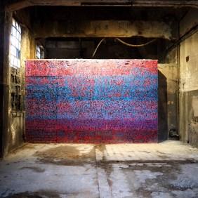 Rot und blau, beleuchtetes Bild von Tanc in einer Halle.