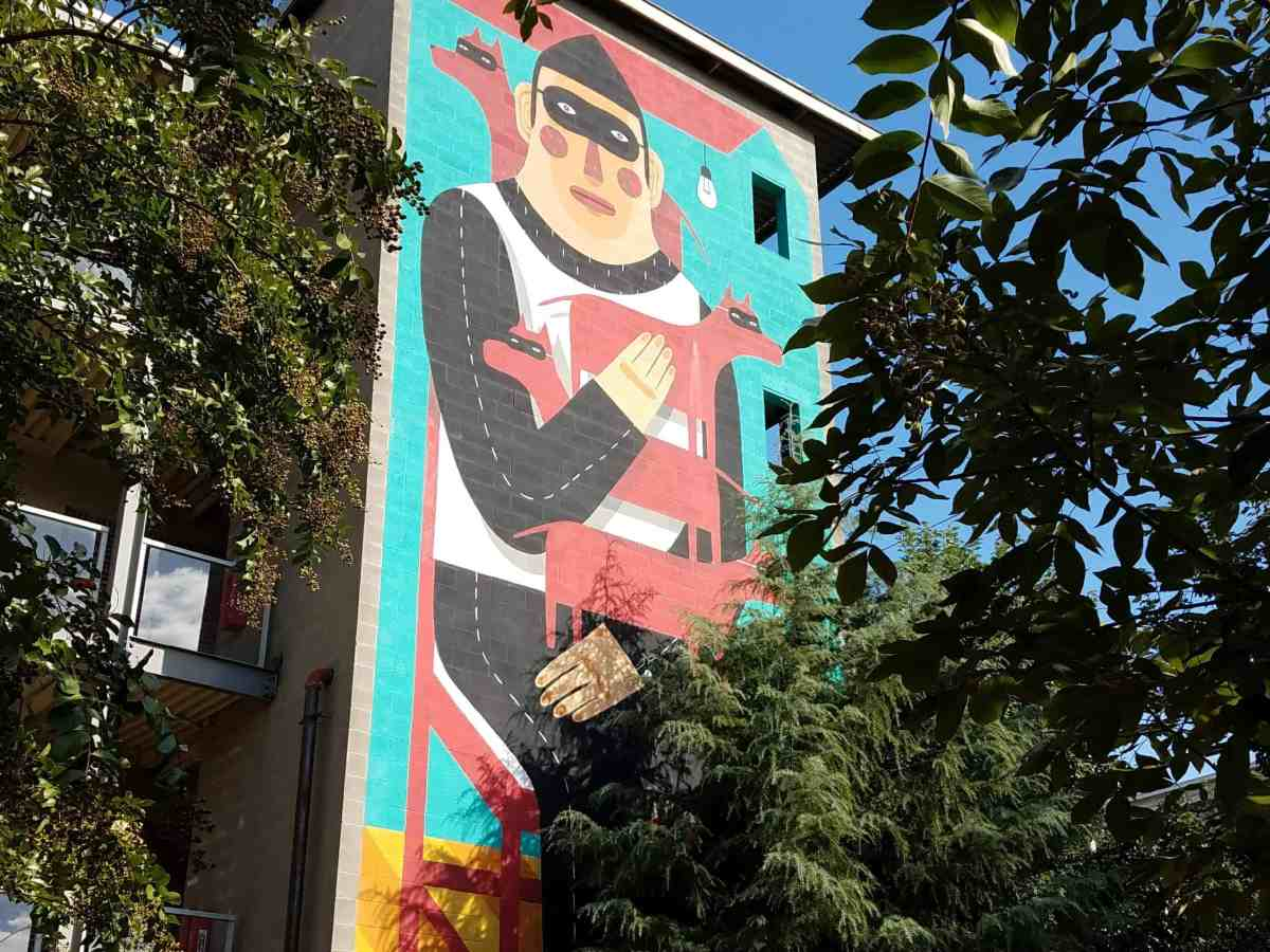 Mural of a masked man holding masked dogs by Agostino Iacurci