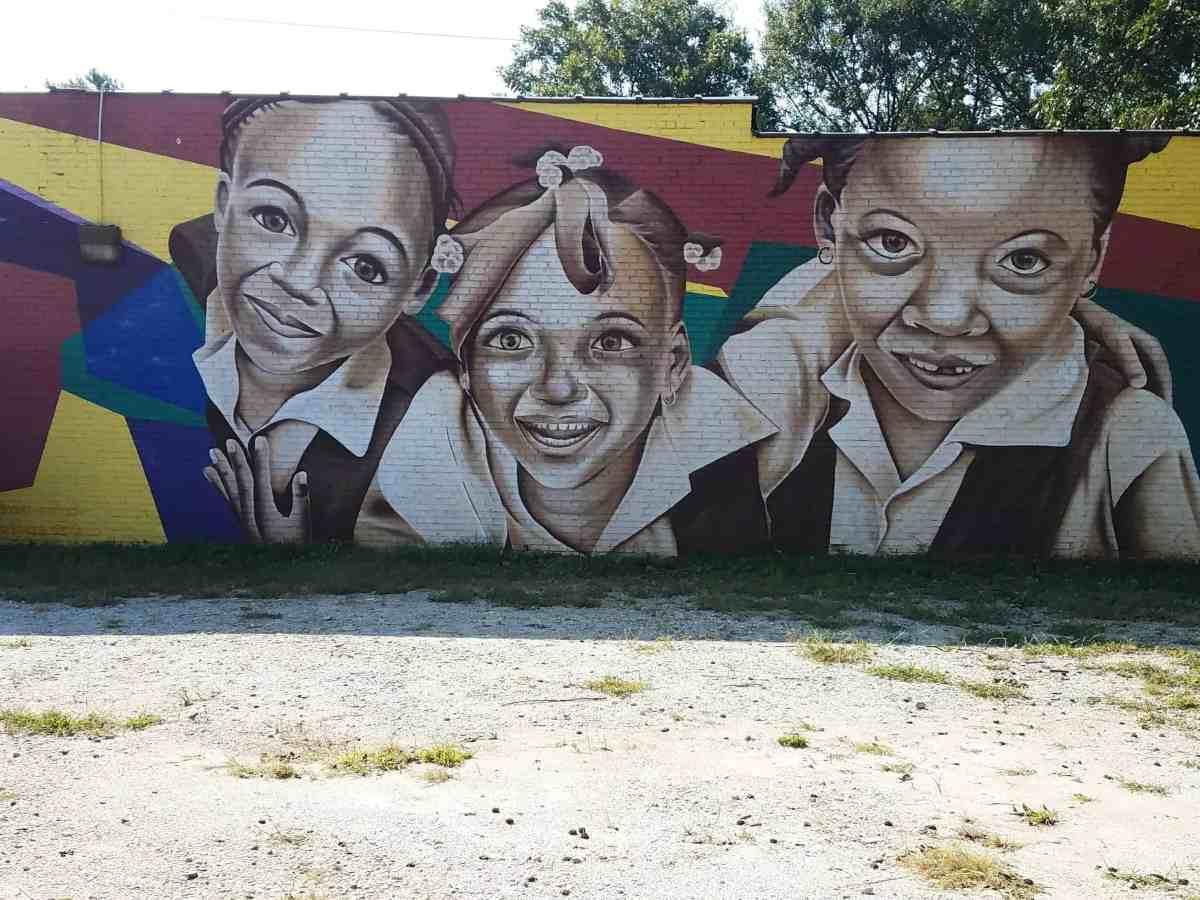 Street art featuring 3 kids by artists Andrzej Urbanski and Indigo