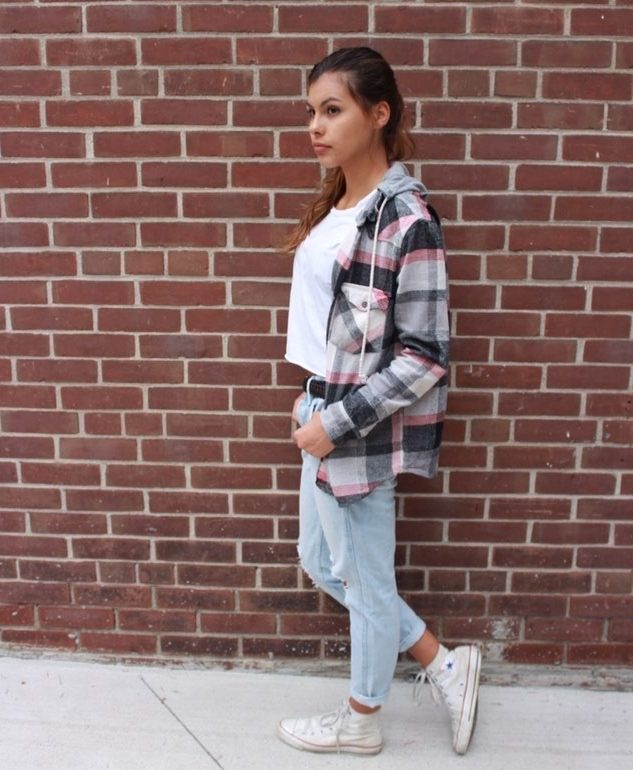 Kat , a young fashionable aboriginal womain in Canada, against a red brick wall