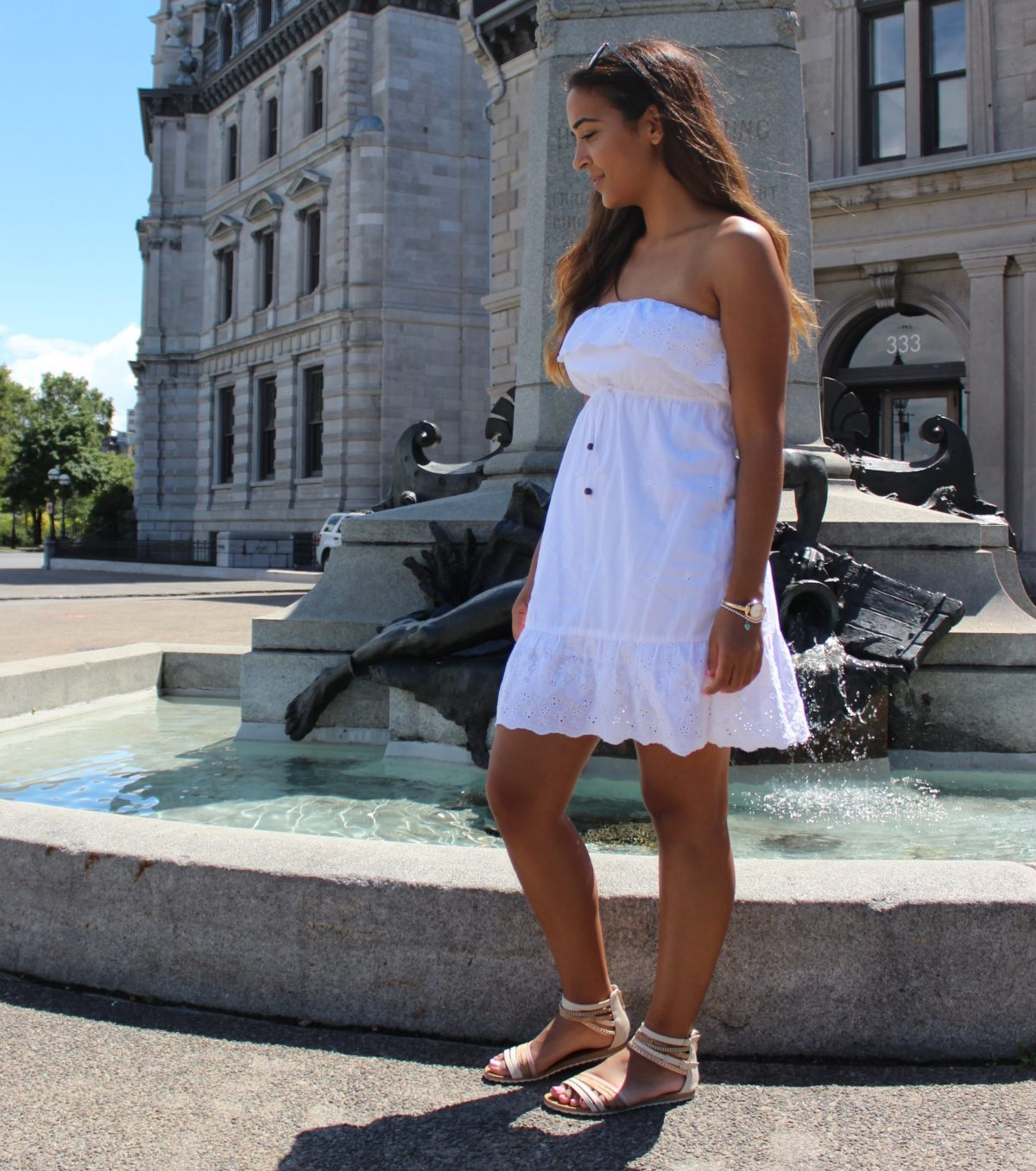 white cotton dress beside old fountain in Montreal