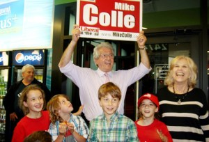 Mike Colle raises an election sign in triumph