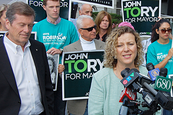 Jaye Robinson speaking at campaign event, with John Tory looking on.