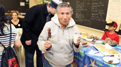 ALEX enjoys a barbecue pork skewer at the spring bazaar.