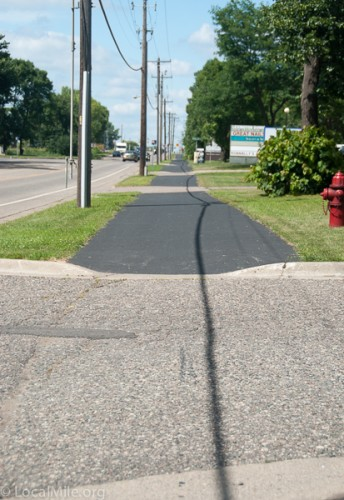 Would you want to ride along this path? Not only is there a jarring bump with every one of those curb cuts but you can't ride side-by-side with a friend. This also indicates that cars in these driveways have right-of-way.