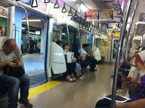 Inside a typical Japan Railways commuter train. Much of the day the aisle is full of standees.