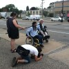 Two wheelchairs being videotaped on broken sidewalk