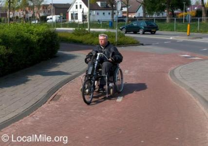 A hand cycle attachment increases the speed and range of a wheelchair, and allows its user to travel with the chair so it can be used at the destination. It may have electric assist. The cycling infrastructure means the person using it doesn't come into conflict with pedestrians.
