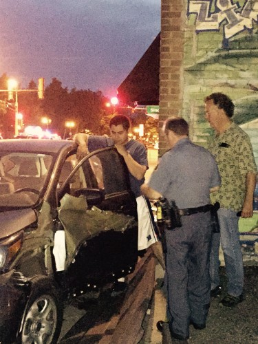 Police officer talks to driver who crashed his car into the front of Dunn Brothers
