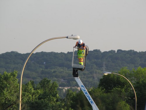 Relamping a shallow glass luminaire on a davit pole, I-35W and 106th Street, Bloomington.