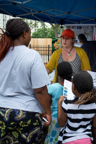 Community Development Coordinator Meg Beekman speaks with people about Eighth Avenue improvements. / Credit: James Warden