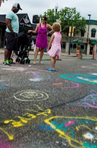 A family enjoys sidewalk chalk at Hopkins' Artery event. / Credit: James Warden