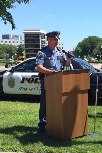 Police officer standing at a podium speaking with a police car in the background