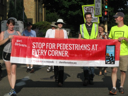 People crossing a street on foot holding a banner that says Stop for pedestrians at every corner.