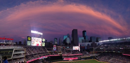 A sunset provides a dome of pink clouds on Target Field during a Twins game.